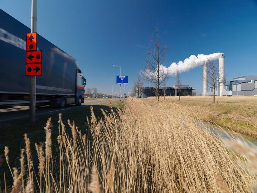 Foto van vrachtwagen rijdend door industriegebied met rokende schoorstenen op de achtergrond